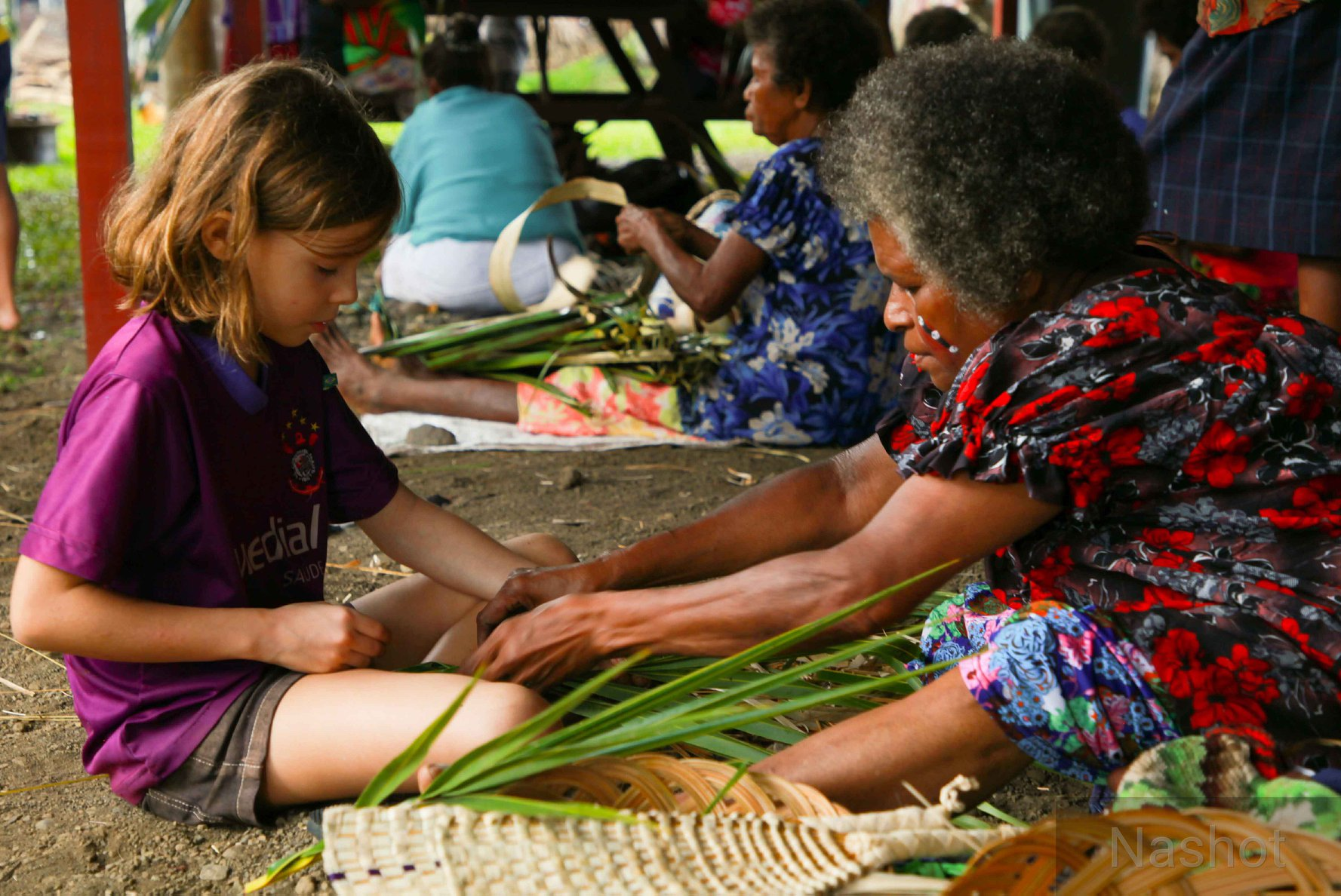 A Milne Bay master weaver showing a child how to weave.